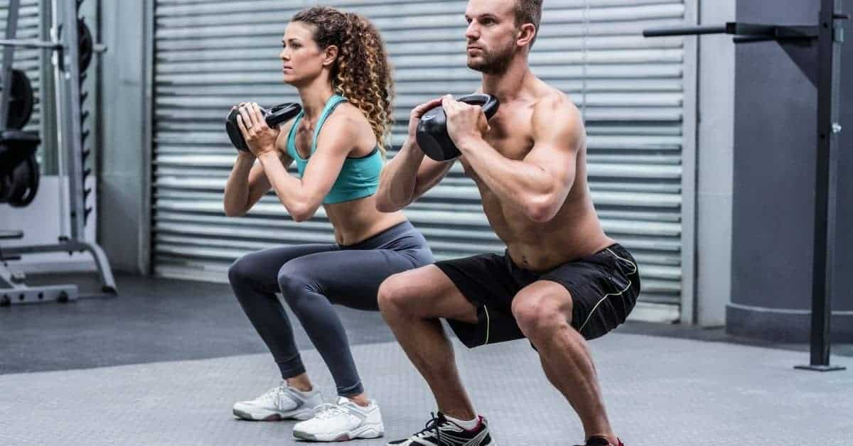 Two people doing weighted squats in an exercise room.